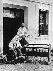 Slovenská matka kolébá své dítě. Babička, která stojí za nimi, je oblečena v pohodlném kabátku z ovčí kůže s vlnou obrácenou dovnitř. Je to příjemné a vypadá to dobře. A babička to ví.