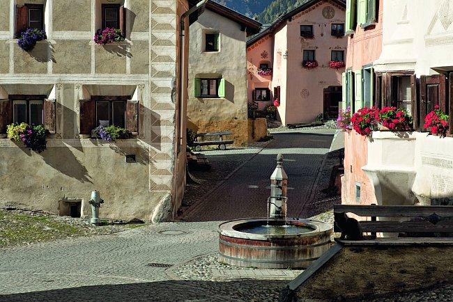 Turisty ohromí tradiční architektura a domy zdobené typickými sgrafiti.