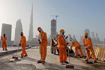Nejvyšší budova nasvětě Burdž Chalífa se tyčí jako vzdálený bajonet nad dělníky zametajícími staveniště. Pocházejí většinou zPákistánu aIndie.