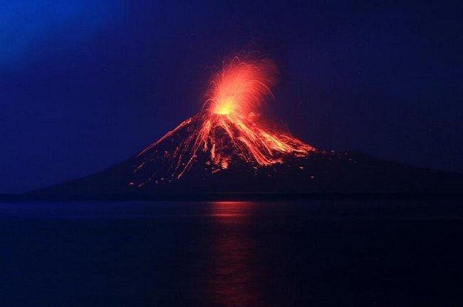 """Pohled na stékající lávu po svazích sopky Anak Krakatau (""""Dítě Krakatoy"""") z blízkého ostrova v Indonésii během červencové erupce."""