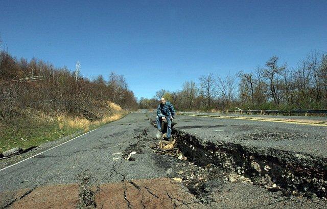Rozervané silnice z nichž vychází dým - běžný obrázek Centralie dnes.