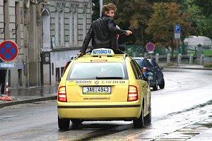 Známý zpěvák a herec coby akční hrdina na střeše auta.