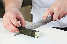 5. Pokud jste pokračovali správně, získali jste rolku, která se nerozpadá. Nyní ji budete krájet. Vezměte ostrý nůž, namočte ho do vody (jinak se vám na něj nalepí rýže a sushi si můžete zničit). Rolku rozkrojte vpolovině a obě půlky ještě překrojte na 3