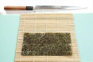 1. Nejprve si dobře umyjte ruce, protože hygiena je při přípravě sushi na prvním místě! Pak si připravte dvě bambusové podložky (budete připravovat jednu rolku slososem a druhou sokurkou) a na každou položte jeden plátek řasy Nori, lesklejší stranou dol