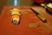 Navrch rolky rozložte na tenké plátky nakrájené avokádo, krevety Ebi (blanšírované sushi krevety), plátky lososa a tuňáka.