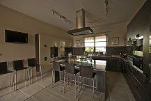 Kuchyně s barovým pultem je vysoce moderní, praktická a prostorná.