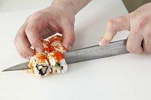 6. Sushi opatrně pevně zarolujte – dávejte si ale pozor, abyste náplň po stranách nevytlačili ven. Namočte nůž a rozkrojte na šest porcí.