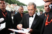 Obklopen ochrankou rozdával hollywoodský herec ve smokingu podpisy nadšeným fanouškům.