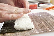 1. Nejprve si bambusovou podložku obalte potravinovou folií. Pak na ni položte půlku řasy, lesklou stranou dolů. Na celou její plochu prsty naneste 110 g rýže (nezapomeňte si namáčet ruce vmisce svodou).
