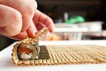 4. Nyní sushi zarolujte. Podložku chyťte zespoda a sushi začněte pomalu pevně zavinovat. Důležité je na sushi přehnaně netlačit, ale jen lehce zamotat. Rolku přimáčkněte zboku a seshora, aby dostala tvar a konec řasy se dobře přilepil.