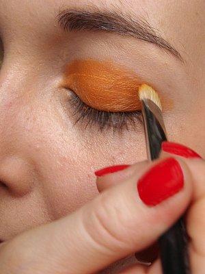 1: Sytě oranžový oční stín rozetřete přes podkladovou bázi po celém pohyblivém víčku, dejte pozor, aby byla barva kompaktní.