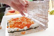 3. Volnou polovinu podložky přiklopte na rýži skaviárem, pevně uchopte a otočte tak, aby byla rýže skaviárem dole na fólii a řasa nahoře.