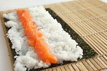 2. Vezměte 75 g uvařené sushi rýže a naneste ji na řasu. Na vzdálenějším okraji řasy nechte volný centimetrový proužek – tam se pak řasa po zarolování slepí ksobě (řasu nenamáčejte). Rýži lehce potřete wasabi, posypte sezamovým semínkem a poklaďte vjedn