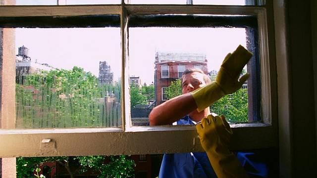 Muž myjící okno