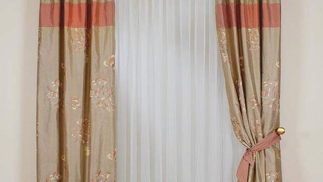 Hedvábné závěsy ušité ze tří barevně sladěných látek a zdobené dvoubarevnýmikvěty, doplněné dvojicí pruhovaných polštářků jsou od firmy Dorian Dekor.