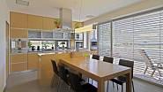 Kuchyně je zařízená v příjemných teplých barvách a je propojena s jídelnou, kterou tvoří velký dřevěný stůl a kožené židle.
