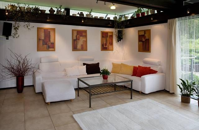 V obývacím pokoji je položená dlažba, sedací soupravu zvolili majitelé domu v bílé barvě. Barevnými doplňky interiér zateplili.