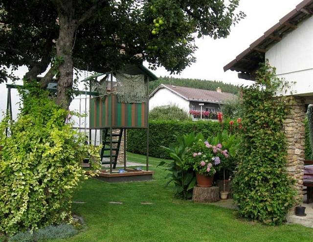 Zahrada plná květin - Jabloň obrůstá dřišťál, nároží garáže skrývá bohatě se ploucí clematis