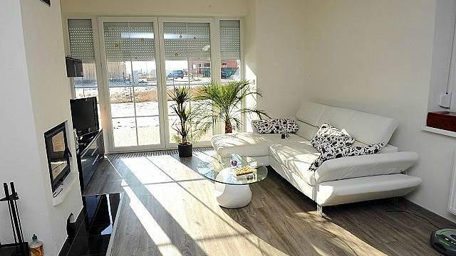 Obývacímu pokoji vévodí bílá kožená sedačka a krb. Hlavní barvou obývacího pokoje je bílá barva.
