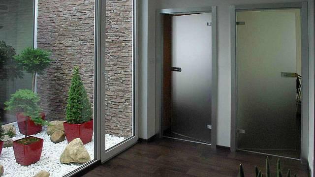 Prosklenné dveře a atrium dům výrazně odlehčují a prosvětlují.