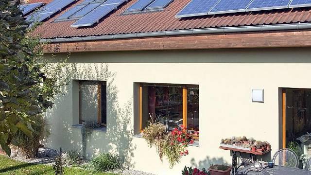 Pohled za zahrady na jižní fasádu domu, na střeše střešní okna VELUX, solární panely BAXI a panely FVE.