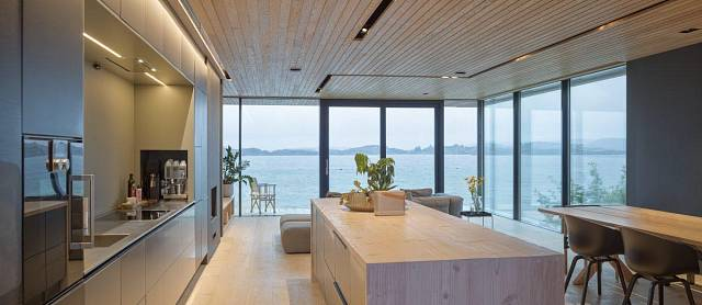Obývací pokoj, kuchyně i jídelna byly sloučeny do rodinného pokoje. V prosvětleném, jednoduchém architektonickém řešení interiéru hraje ústřední roli panorama krajiny. Foto: Sindre Ellingsen