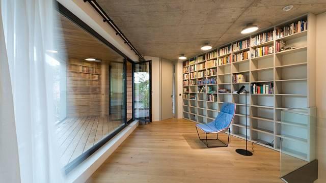 Interiérový minimalismus znábytku na míru vbarvě bílé kávy, šedých pohledových betonů a dubových podlah.