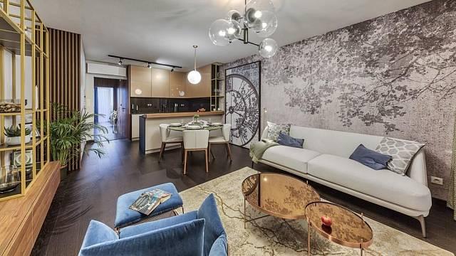 Kuchyň je spojena s jídelnou a obývacím prostorem. Horní skříňky kuchyňské linky vnášejí, svou teplou barevností a zrcadlící se plochou v kombinaci s antracitovou šedou, do prostoru eleganci a pocit luxusu.
