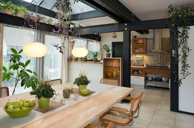 Jídelna i kuchyň jsou dokonale prosvětleny, přiznané trámy podtrhují atmosféru dřevostavby.