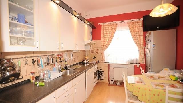 Útulná kuchyň s americkou lednicí a s miskami pro dva pejsky – další členy rodiny.