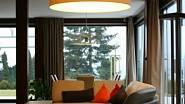 Strohý pravoúhlý půdorys a přísně ortogonální tvary vybavení by příjemně zjemnil kruhový širm svítidla, opakující na stropě tvar konferenčního stolku.