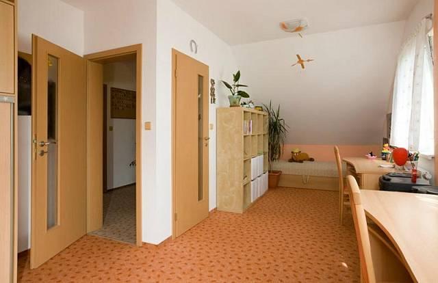 Dětský pokoj je situovaný do horního patra. Vybavený je celoplošným kobercem a dřevěným nábytkem.