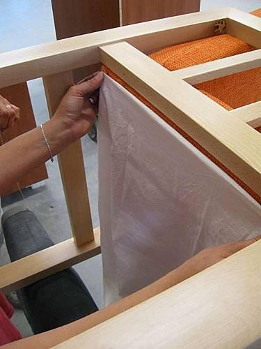 Dřevěnou kostru křesla opět sesadíme. Pak vsadíme sedák, a před jeho pevným spojením s konstrukcí připevníme zespodu na jeho přední hranu začisťovací husté bílé plátno - přišijeme ho v ruce nebo připevníme sponkami či hřebíčky. Sedák přišroubujeme k op...
