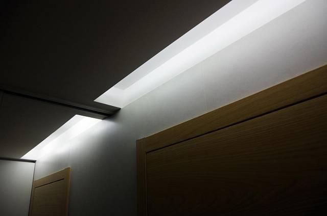 Osvětlení ve sníženém stropě je velmi efektní. Možná ale až příliš je v dlouhé chodbě strop posunutý dolů
