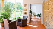 Proutěná křesílka, terakotová podlaha, kamenný obklad a výhled do zahrady vytváří příjemnou domácí atmosféru.