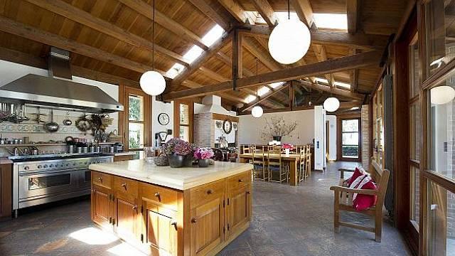 Kuchyně má  místo dřeva na podlaze keramické matové dlaždice a kuchyňská linka v nerez provedení i ve své modernosti vzbuzuje představu jakési rustikálnosti a starobylosti.