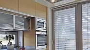 Kuchyni prosvětlují okna. Od jídelní části je kuchyňský prostor oddělen varným ostrůvkem.