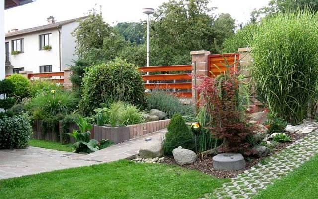 Zahrada plná květin - Předzahrádku zkrášlují dekorativní trávy a dřeviny - japonský javor, okrasná převislá jíva, u vrátek při vchodu kvete levandule