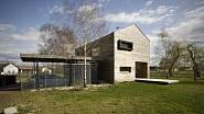 Architektura domu je podpořena terasami vybíhajícími do zahrady, stínící markýzou a krytým stáním.