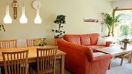 Obývací pokoj je spojený s kuchyní a jídelním prostorem. Dominantou obytného porstoru je červená rohová sedačka s velkým jídelním stolem z masivu.