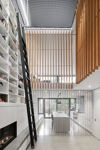 Dlouhý žebřík je nejen fuknční pomocník, ale i designový prvek v bílo-dřevěném interiéru.
