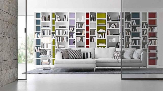 Bílá knihovna v kombinaci s barevnými prvky dodává místnosti lehký a veselý tón a působí velmi hladce a stylově.