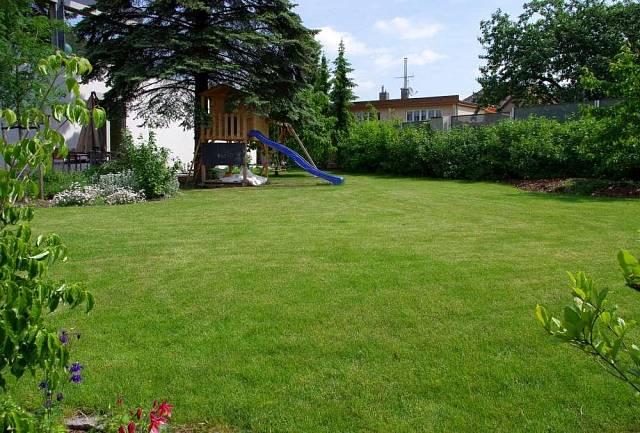 Zahrada si zachovává své soukromí, rozsáhlá travnatá plocha poskytuje dostatečný prostor pro odpočinek i hru. Je zde stín i slunce a lemují ji barevné květy a jedlé plody.
