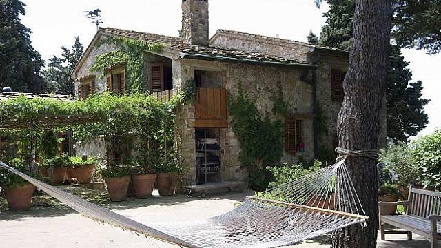 Tradiční kamenný dům středomořského typu s dřevěnými okenicemi a malou dřevěnou lodžií nad otevřeným vchodem.
