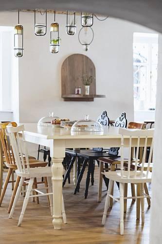 Centrem bistra je velký stůl vyrobený na míru. U stolu se snídá, schází, seznamuje, potkává. Židle jsou z pozůstalosti. Foto: Thomas Skovsende