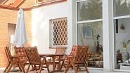 U domu je rozlehlá terasa s bazénem a příjemným zahradním posezením.
