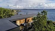 Neprůhledné části obvodového pláště budovy jsou tvořeny fasádními panely a dřevěným obložením v černých, šedých a hnědých tónech. Architekt zde zvolil barvy a materiály z okolní přírody. Foto: Sindre Ellingsen