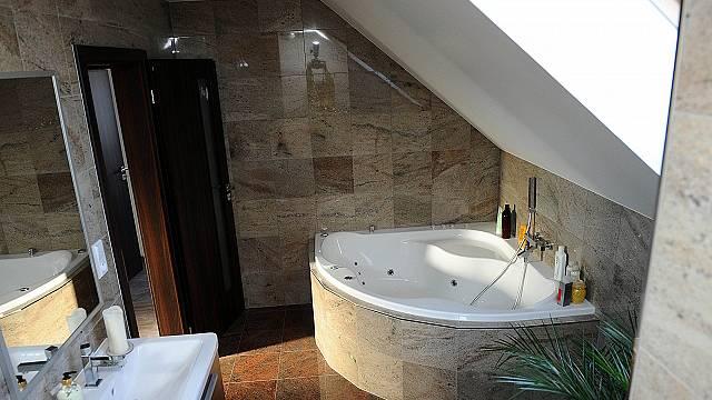 Druhá koupelna je menší, ale spíše relaxační. Najdeme v ní rohovou vanu a tlumené přírodní barvy.