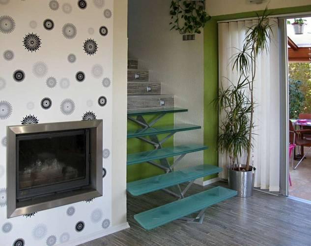 Skleněné schody, vstup na terasu a krb vytváří jakýsi užitkový kout hlavní obývací místnosti