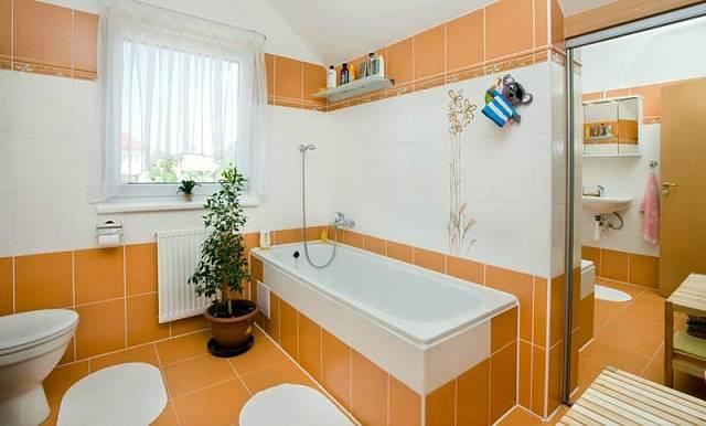 Pro koupelnu manželé zvolili kombinaci bílé a oranžové barvy. Koupelna působí příjemně a teple.